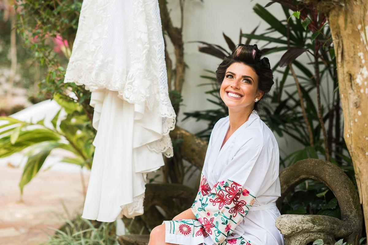 noiva posando ao lado do vestido antes do casamento