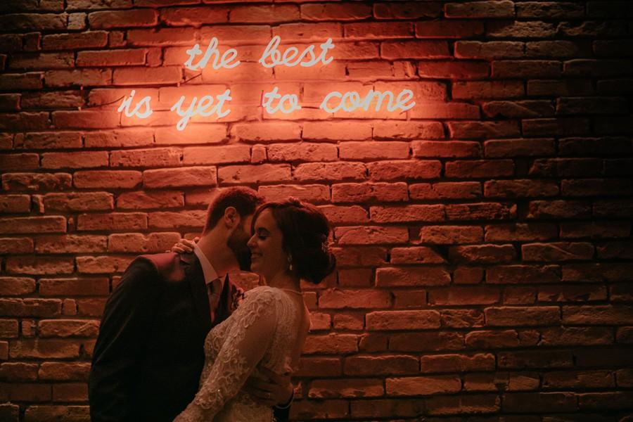noivos posando em frente a um painel luminoso com a frase the east is yet to come