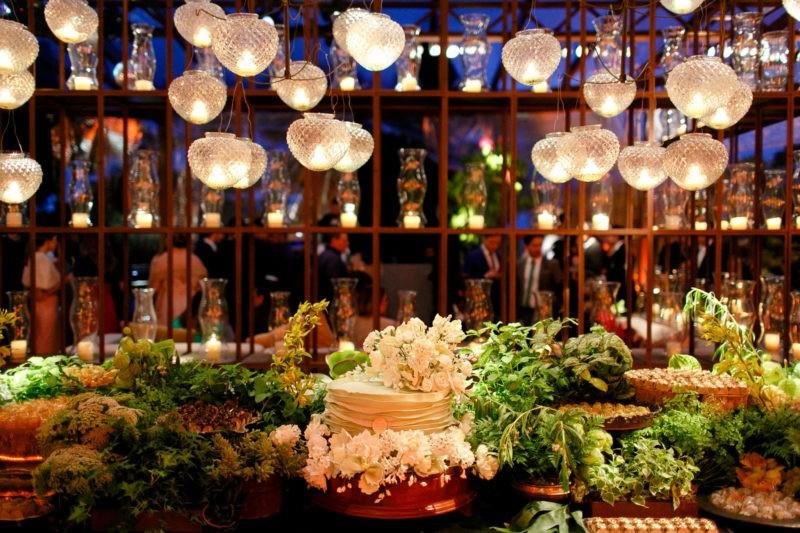 mesa de doces verde e branca com folhagens e lustres