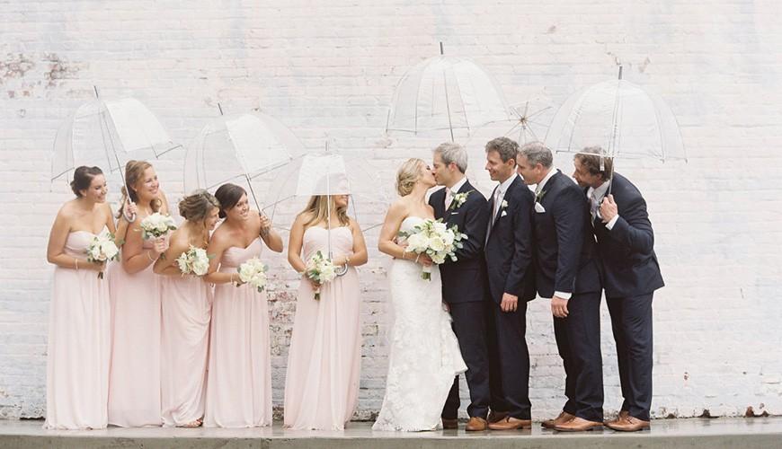 noivos com padrinhos e madrinhas em um casamento na chuva