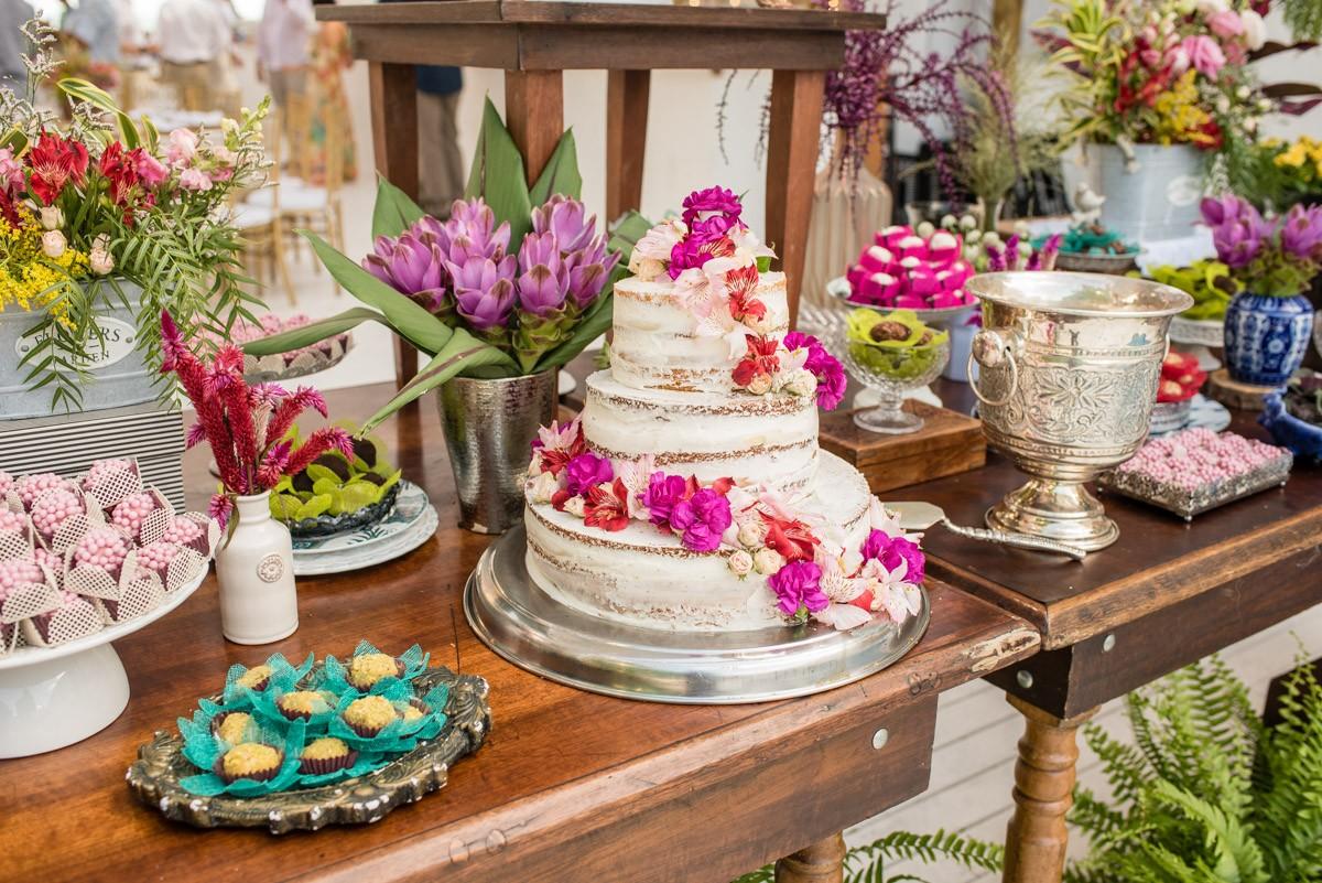 bolo de casamento espatulado com flores na mesa de doces