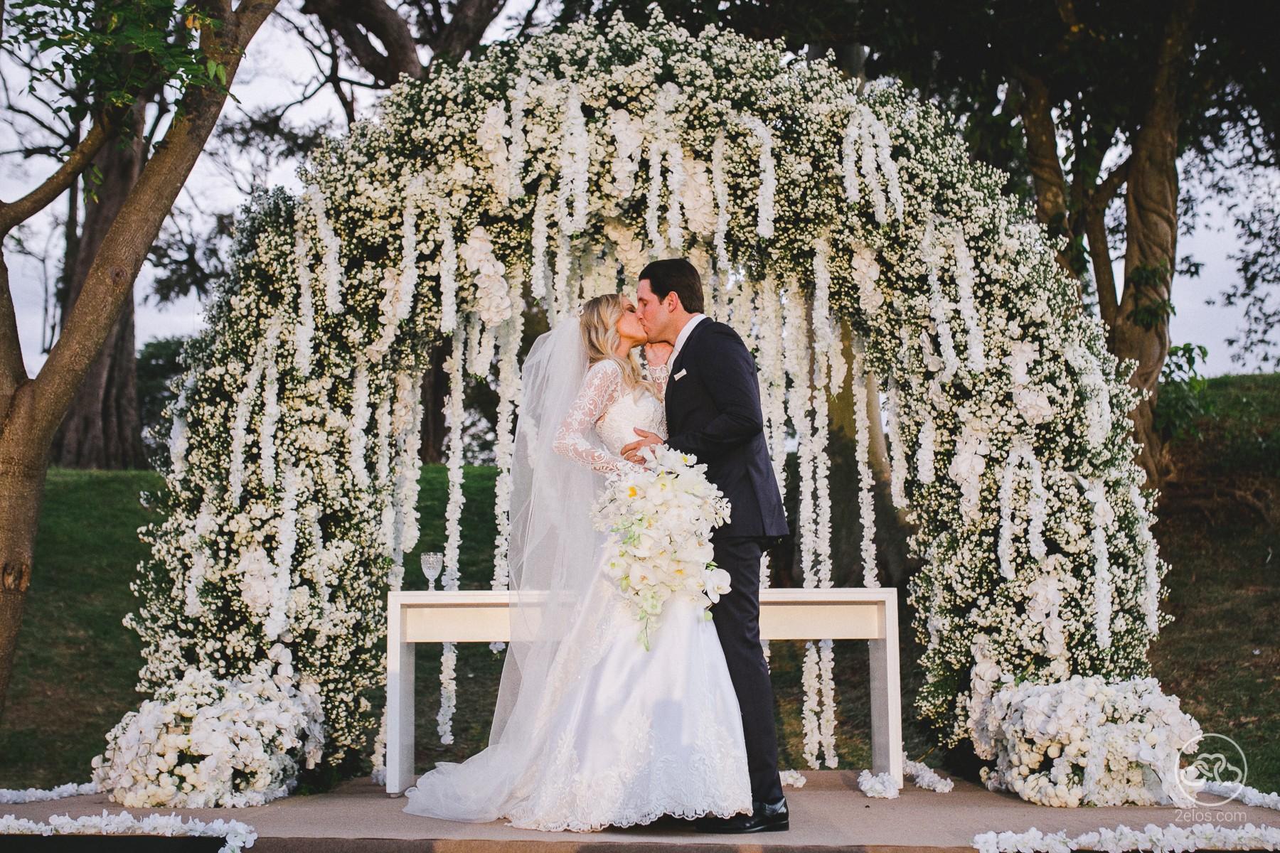 Casal se beijando após cerimônia em casamento ao ar livre.