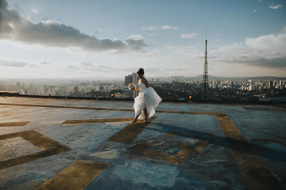 Noiva em rooftop tirando foto com seu vestido após cerimônia de casamento na cidade