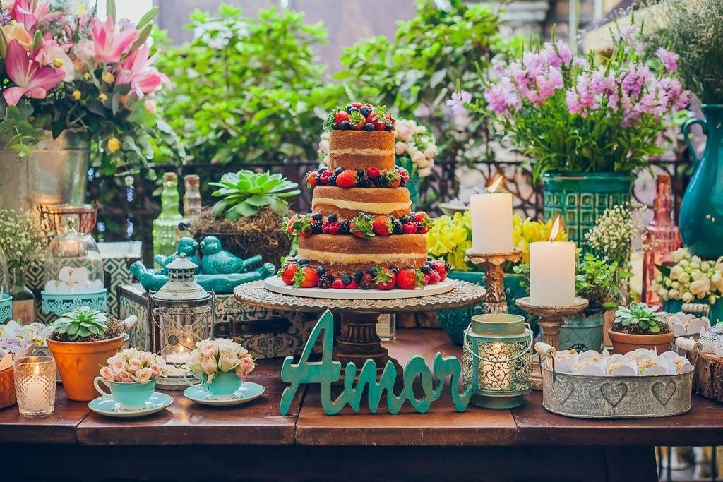 mesa de doces decorada com um bolo naked cake