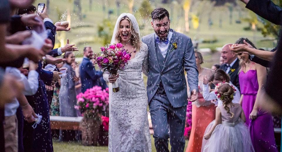 Casal entrando em cerimônia ao ar livre, chuva de arroz.