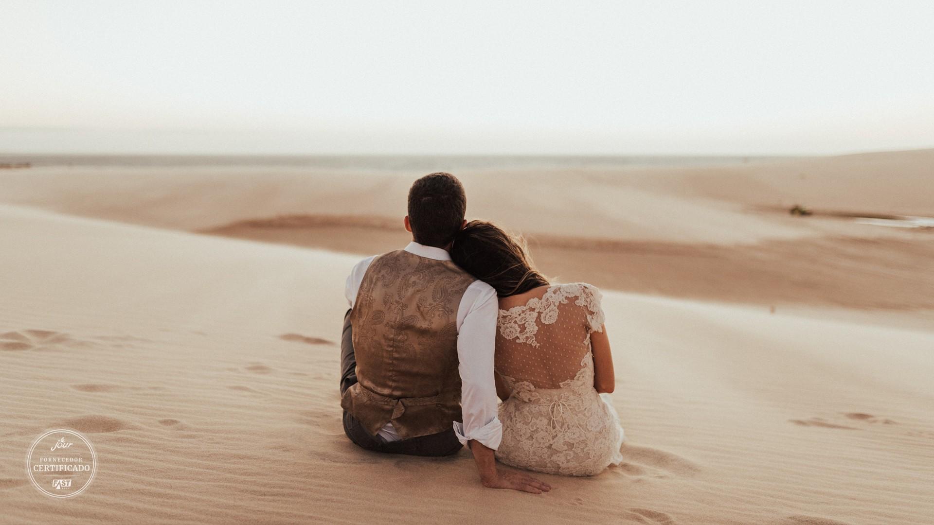 noivos sentados na areia após a cerimônia do casamento na praia