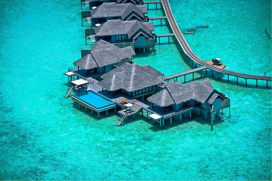 Bangalôs sob água do mar cristalina nas Maldivas.