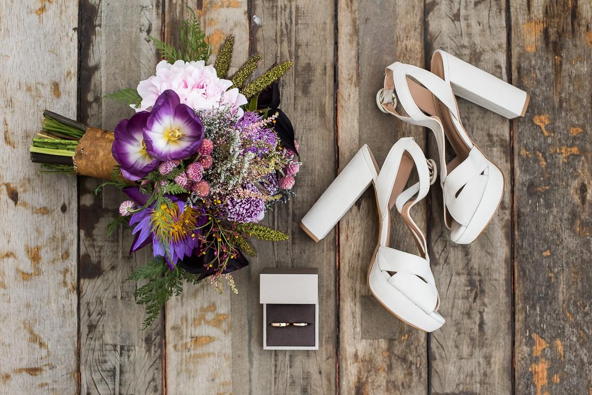foto do buquê com as alianças e o sapato da noiva