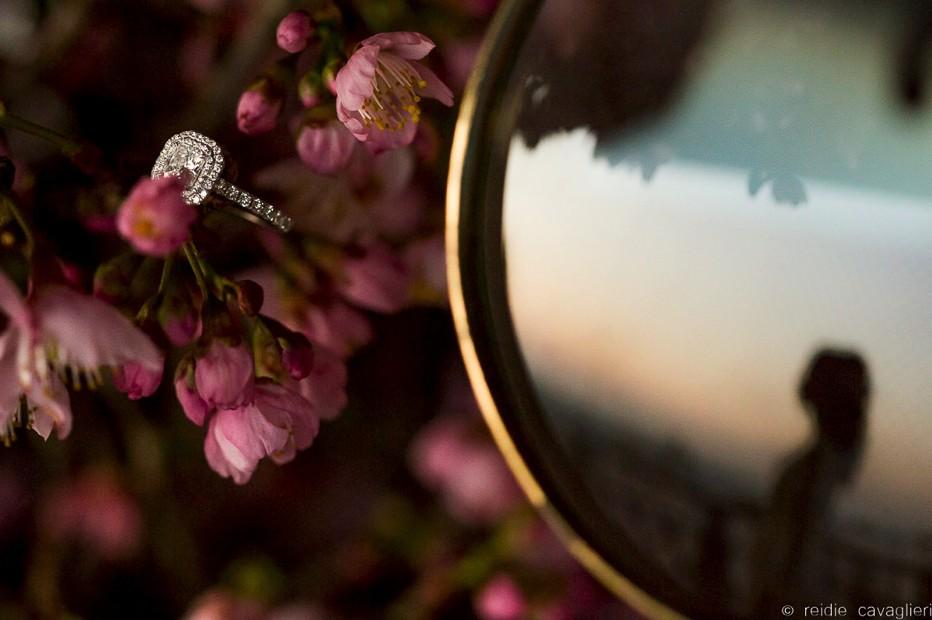 foto do anel de noivado da noiva em meio a um arranjo de flores