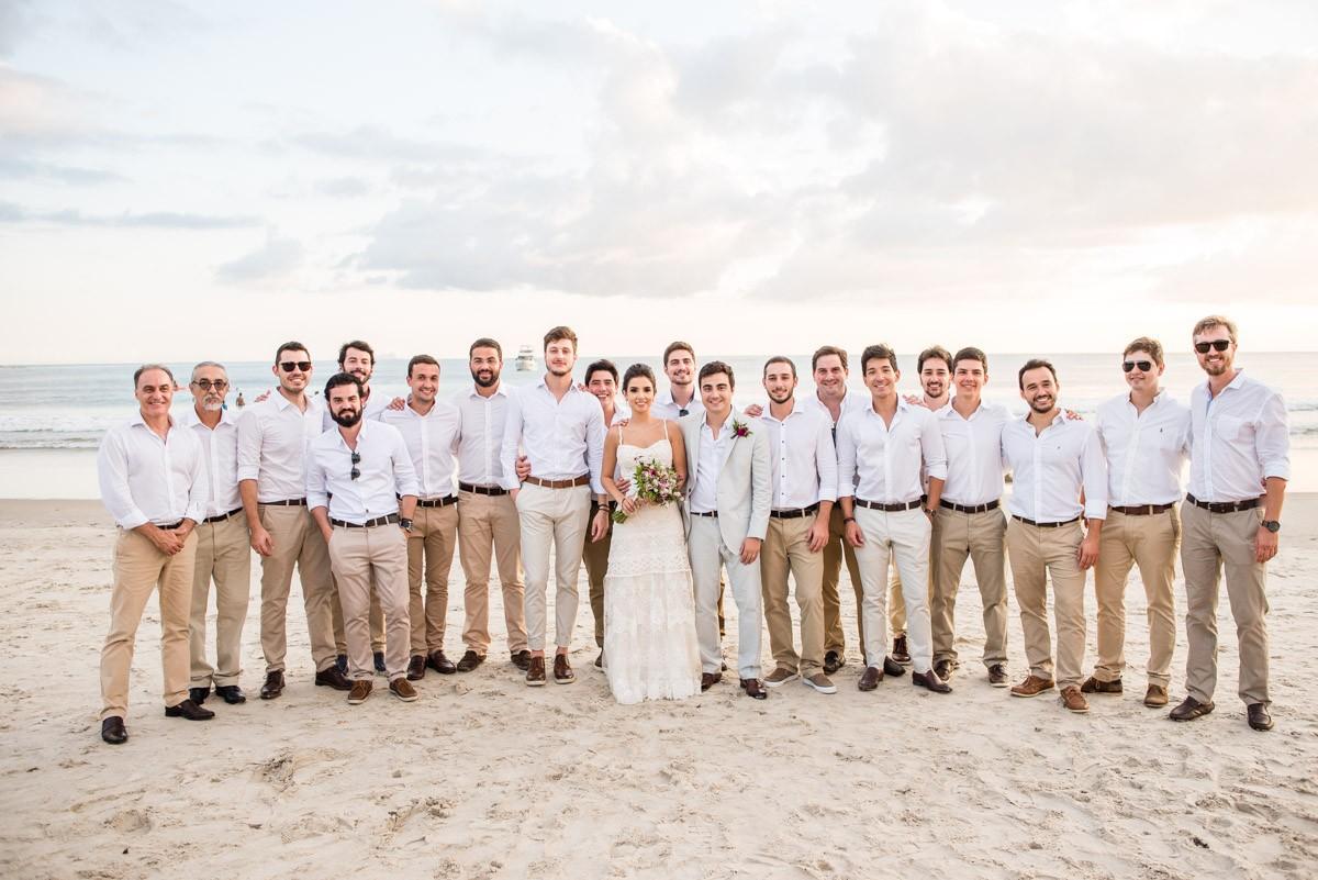 noiva posando com os padrinhos na praia