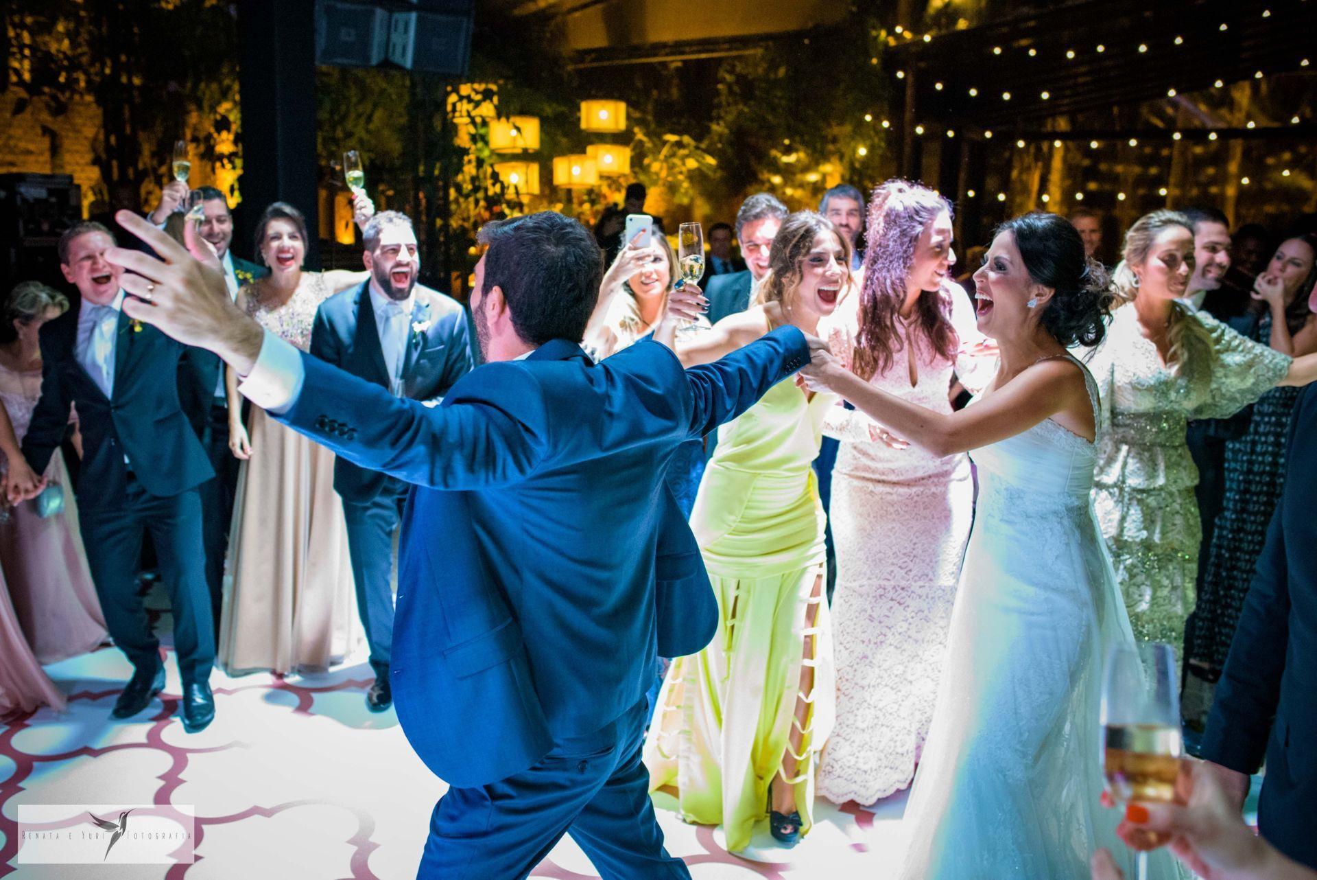 Casal e convidados dançando em pista de dança.