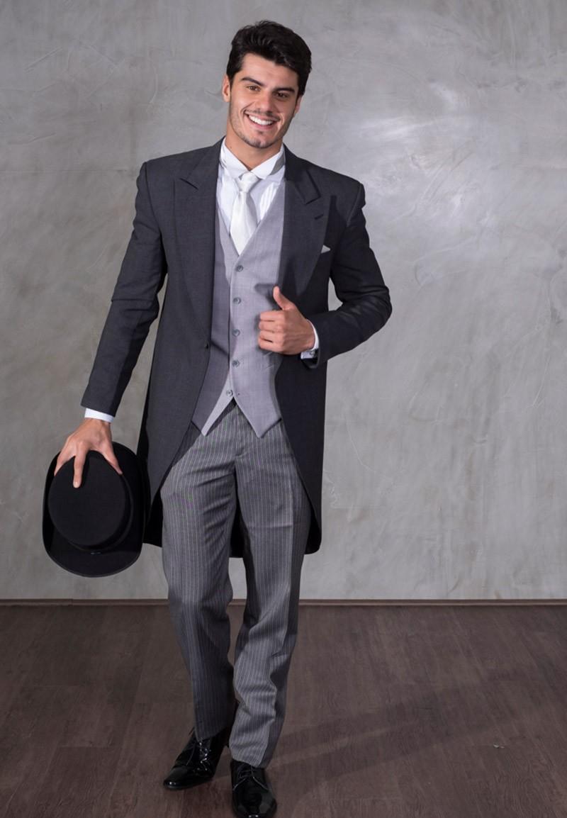 Fraque cinza escuro com colete e calço cinza claro, e chapéu preto.