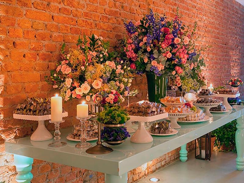 Mesa de doces decorada com flores no espaço da Casa Manioca.