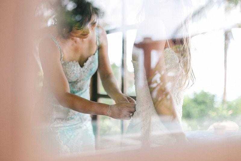 mãe da noiva fechando vestido em ensaio de making of