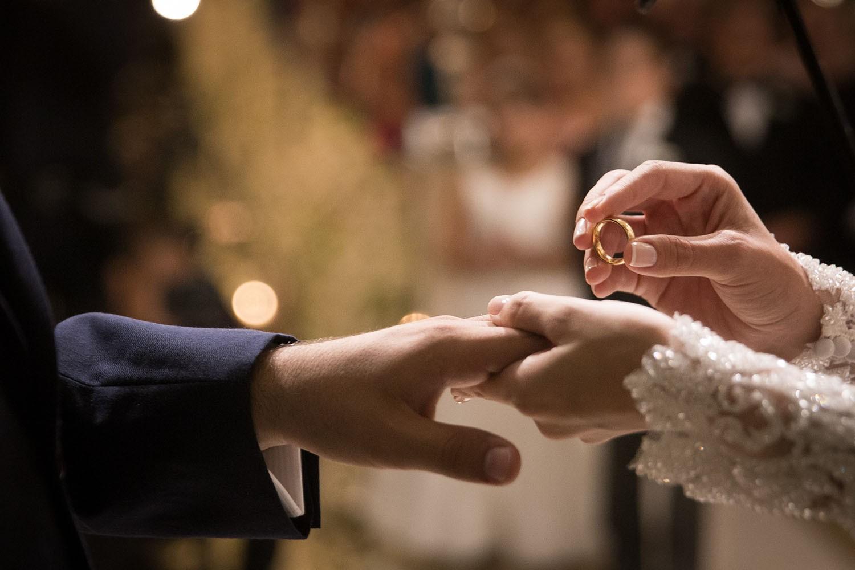 noiva colocando a aliança no noivo durante a cerimônia do casamento