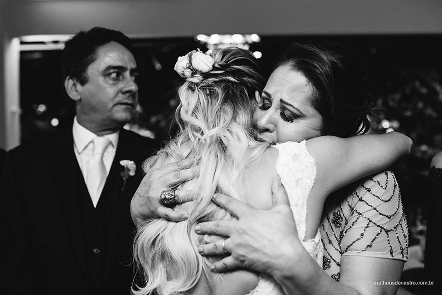 Noiva abraçando mãe após cerimônia de casamento.