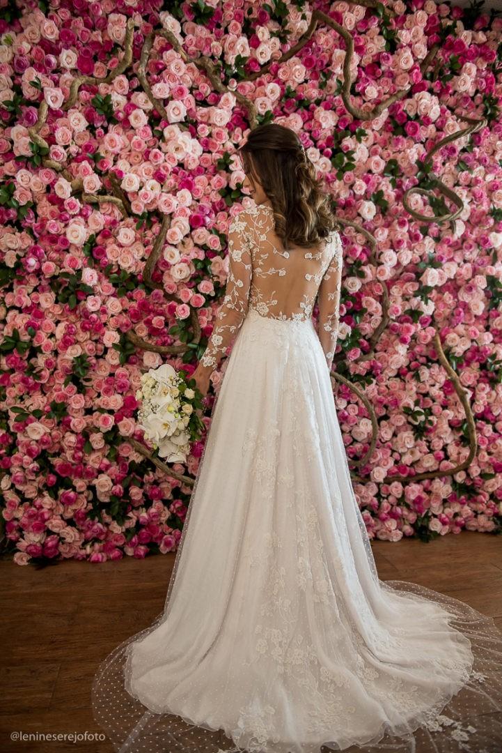 noiva posando com o vestido em frente a um painel de flores
