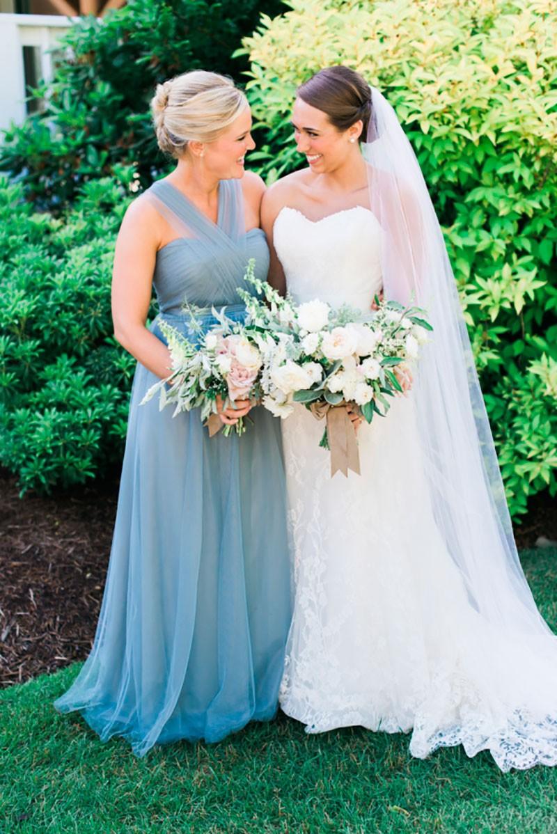 Noiva tirando foto com mãe após cerimônia.