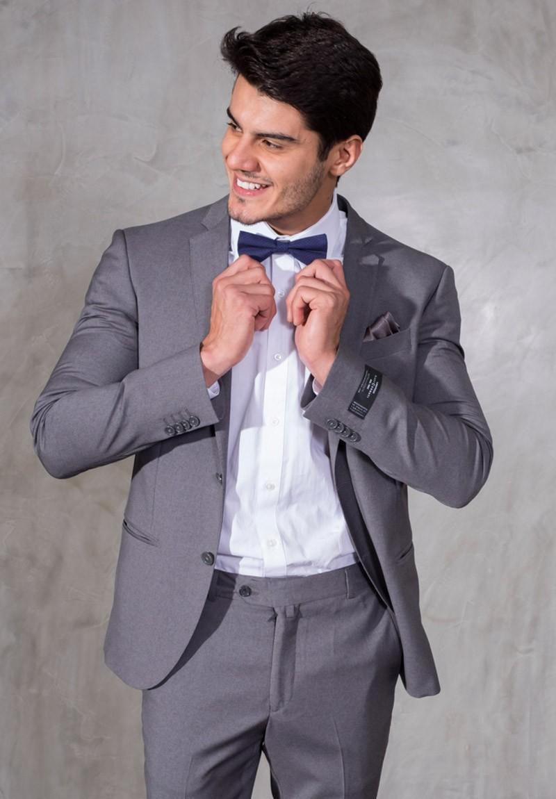 Costume cinza, com camisa branca e gravata borboleta cinza