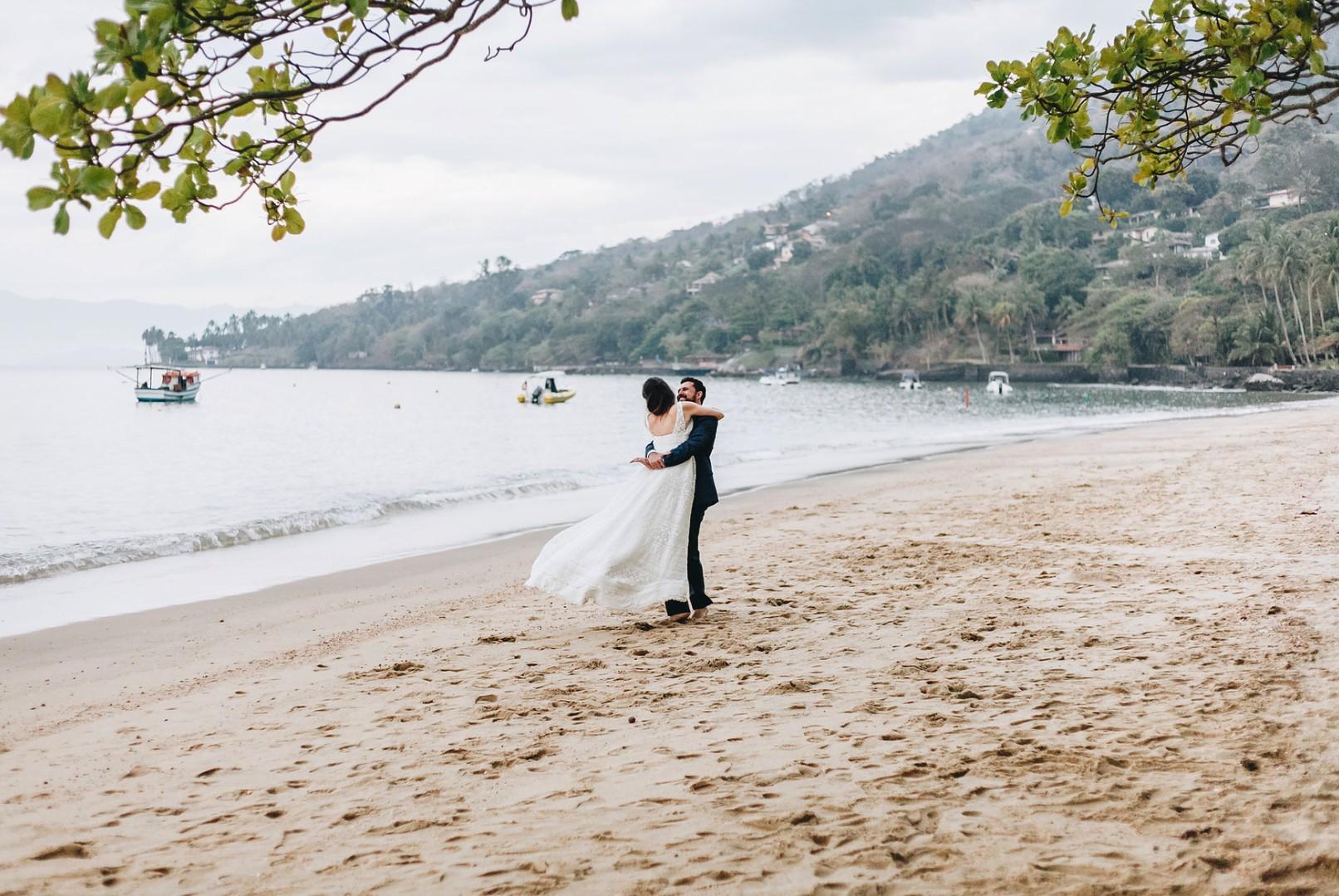 foto dos noivos na praia após a cerimônia do casamento