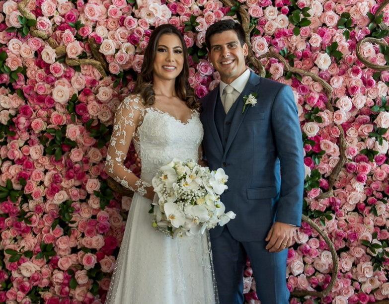 noivos posando em frente a um painel de flores