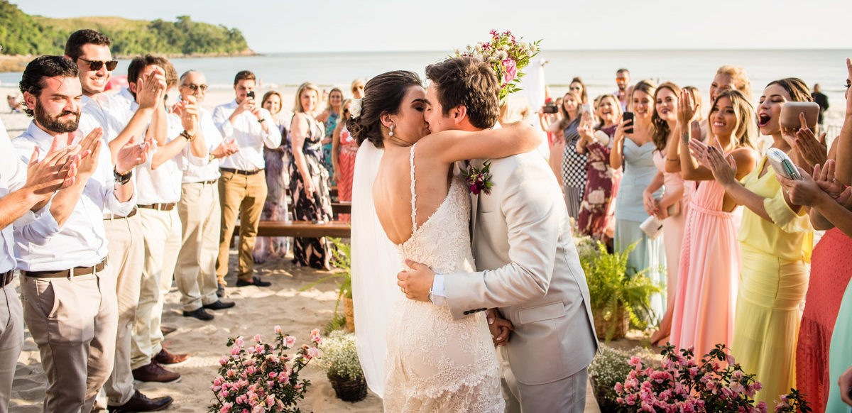 noivo se beijando na cerimônia pé na areia