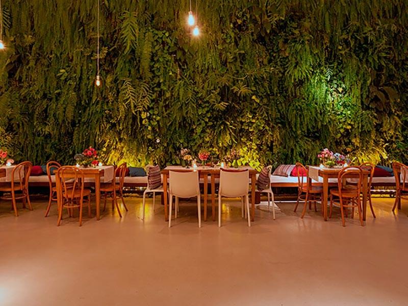 Mesa decorada para convidados em frente a uma parede de flores no espaço da Casa Manioca.