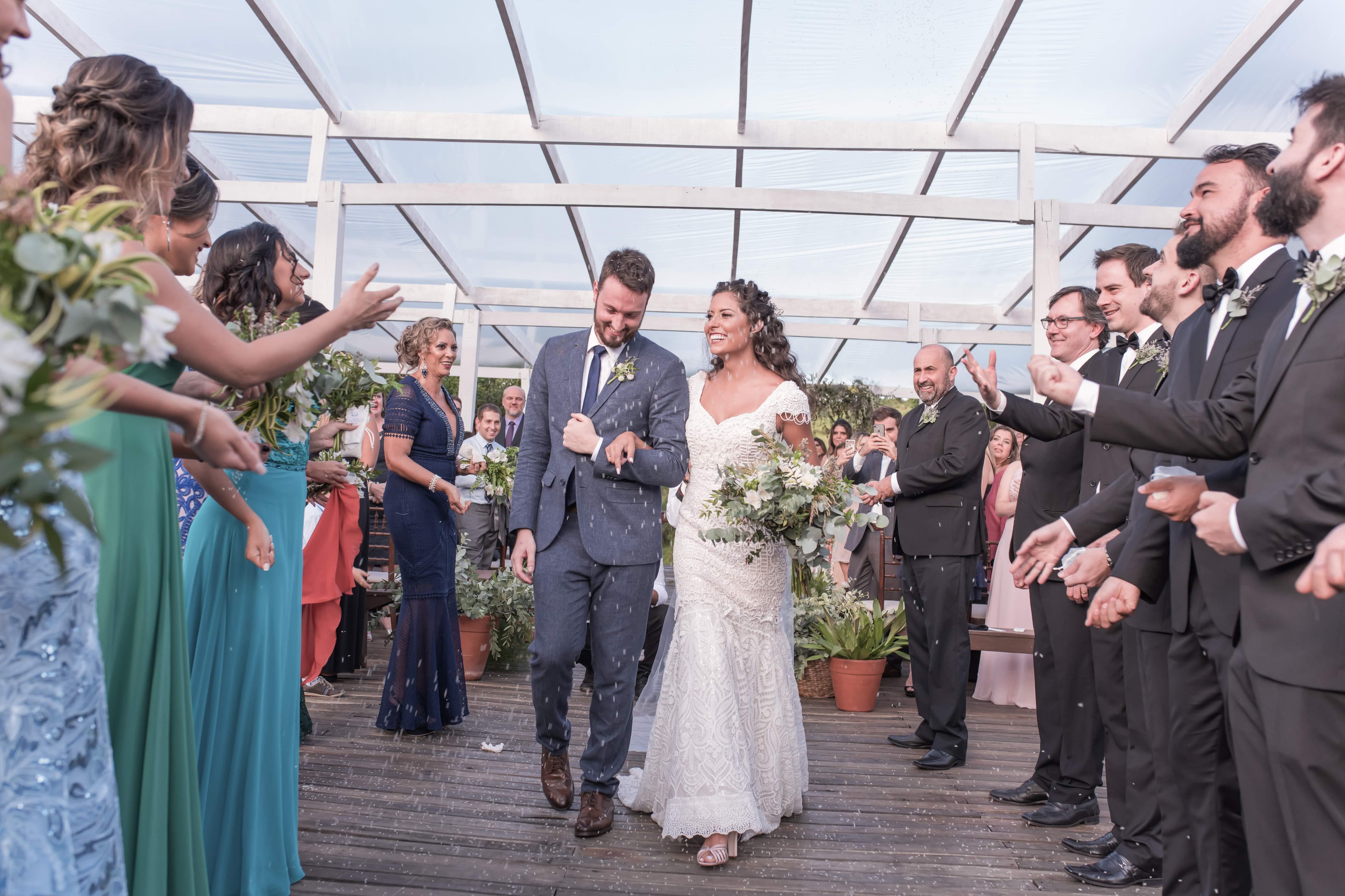 saída dos noivos da cerimônia de um casamento no campo