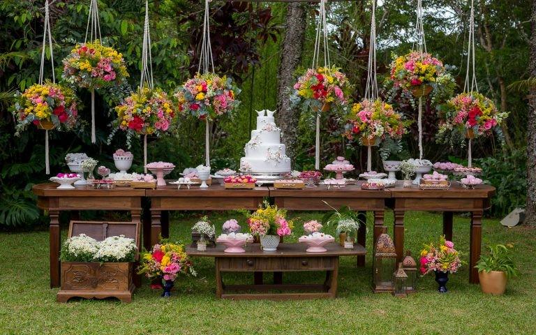 Mesa de doces decorada para casamento rustico no campo.