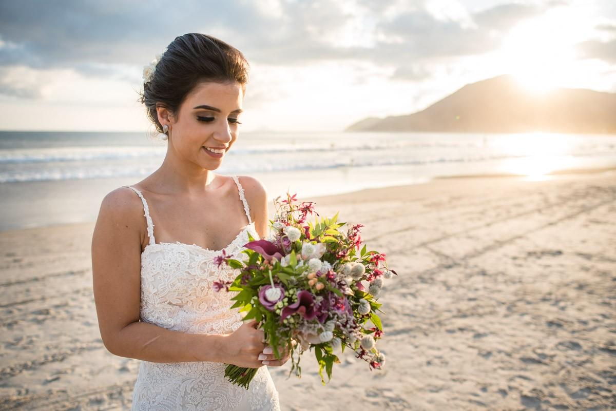 noiva posando com o buquê na praia