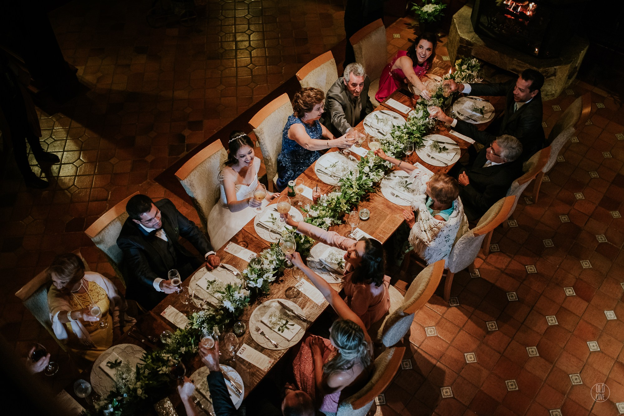 Casal celebrando com convidados na mesa do jantar.