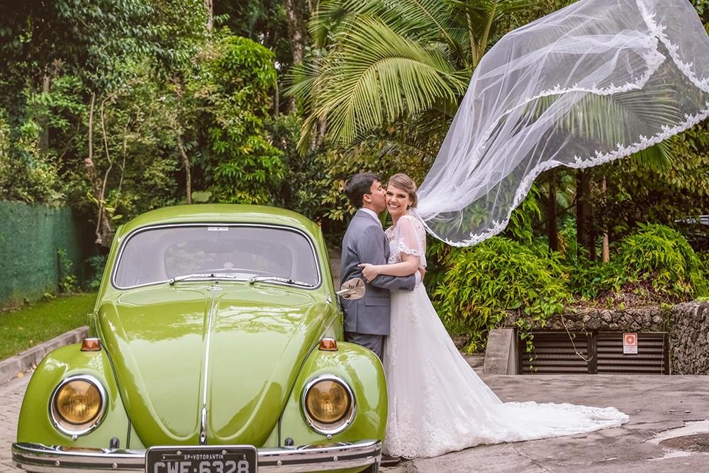 noivos posando ao frente a um fusca após a cerimônia do casamento