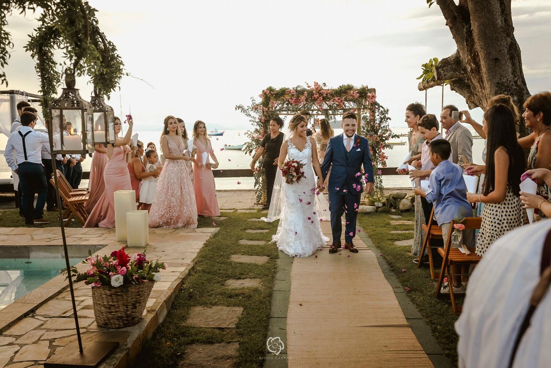 saída dos noivos da cerimônia de um casamento na praia