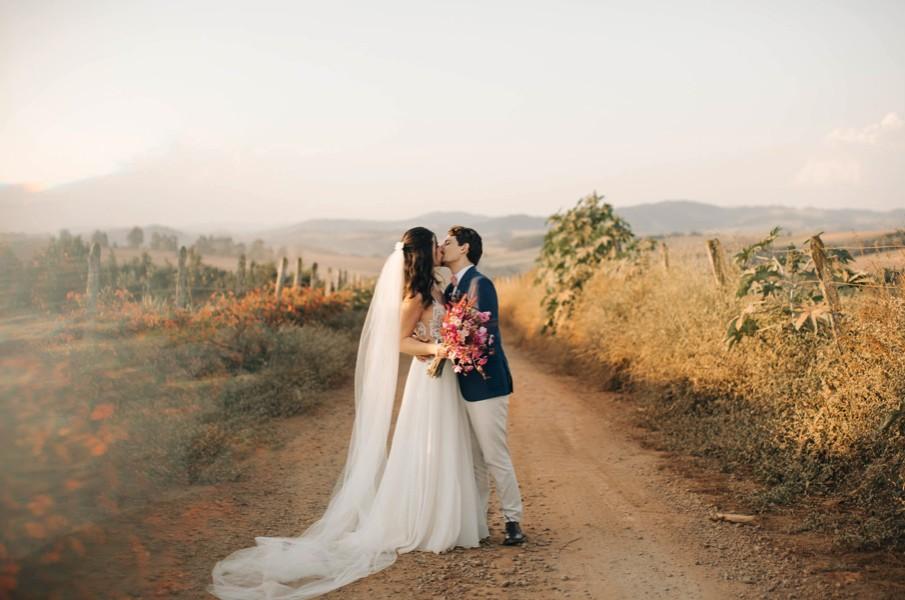 Casal em foto no campo, casamento rústico.