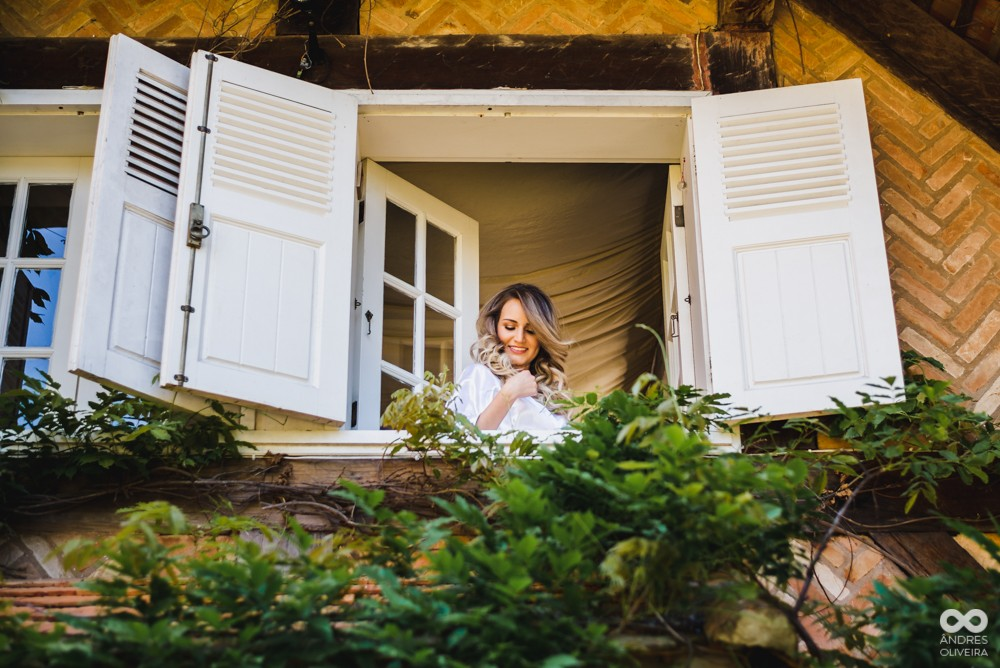 noiva posando na janela antes do casamento