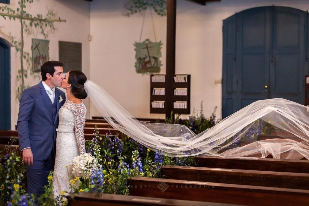 Casal se beijando após a cerimônia. O vestido da noiva tem um véu longo.