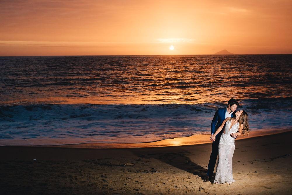 Noivos na praia posando para as fotos do casamento