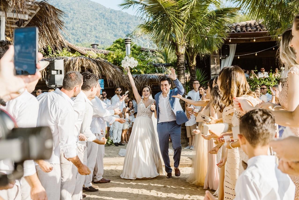 saída dos noivos da cerimônia de casamento na praia
