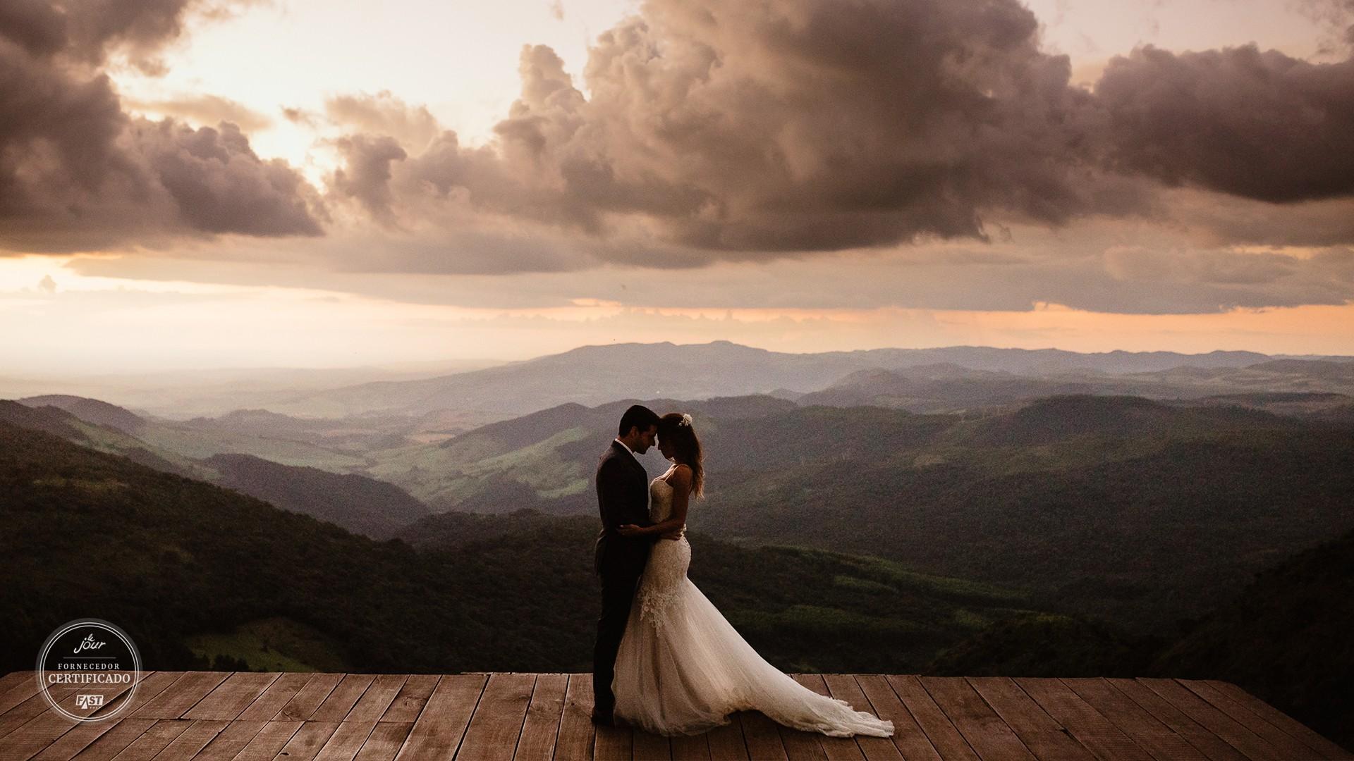 casal posando ao por do sol em um casamento no campo