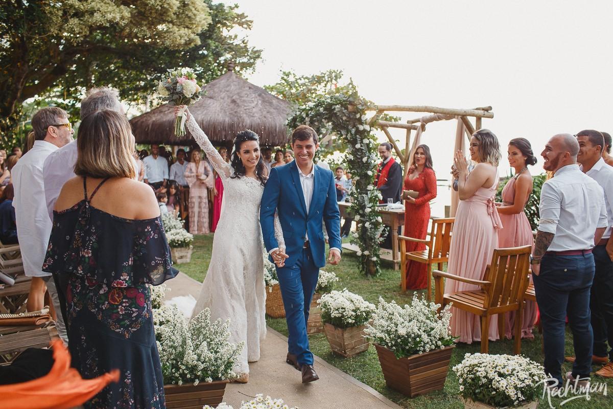 Noivos saindo da cerimônia em casamento rústico na praia