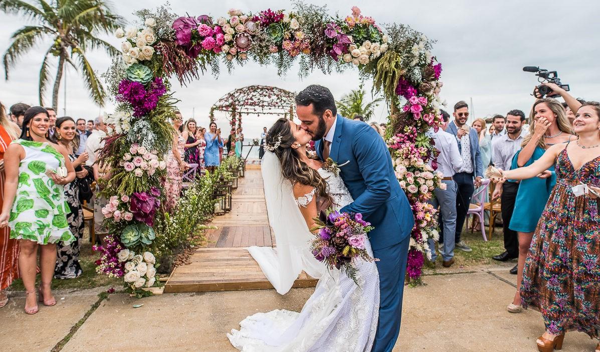 noivos se beijando na cerimônia de um casamento na praia