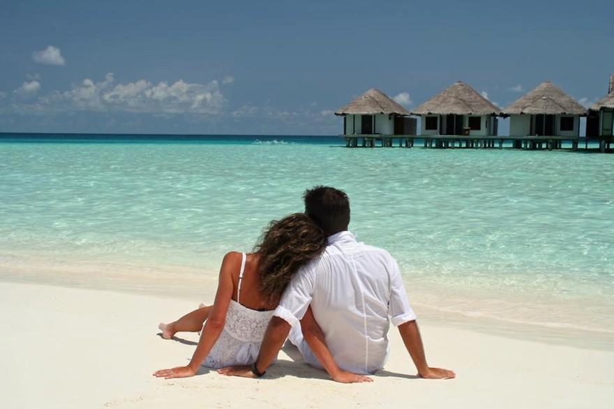 Casal juntos olhando o mar em praia paradisíaca, destino de lua de mel.