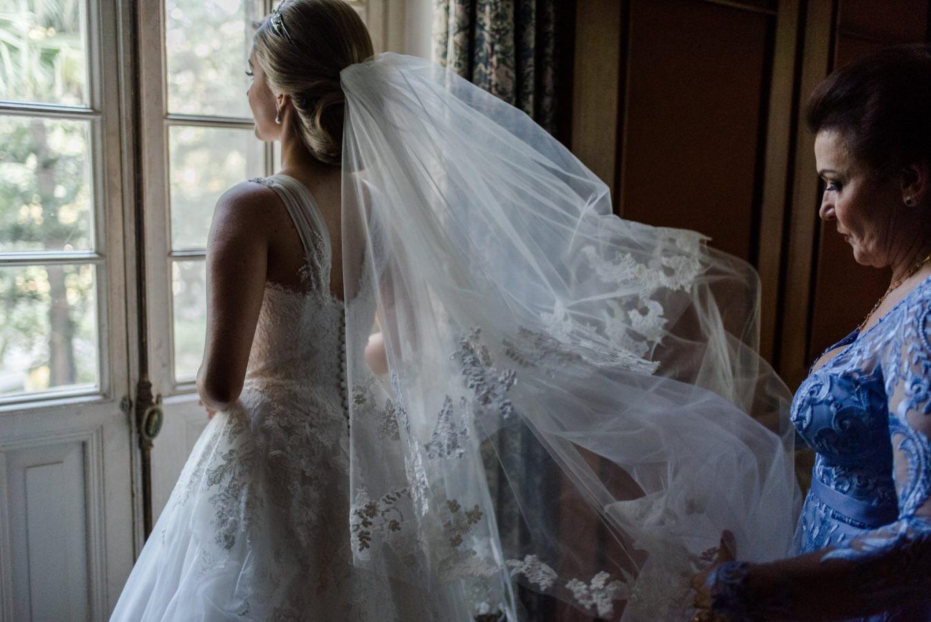 mãe ajudando a noiva com o véu no making of do casamento