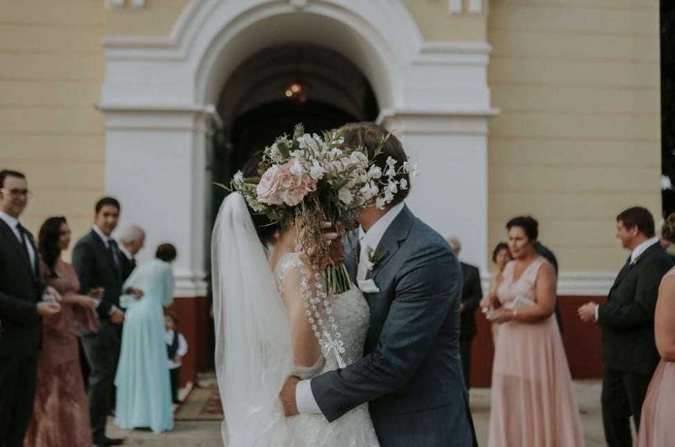 beijo dos noivos na saída da cerimônia da igreja
