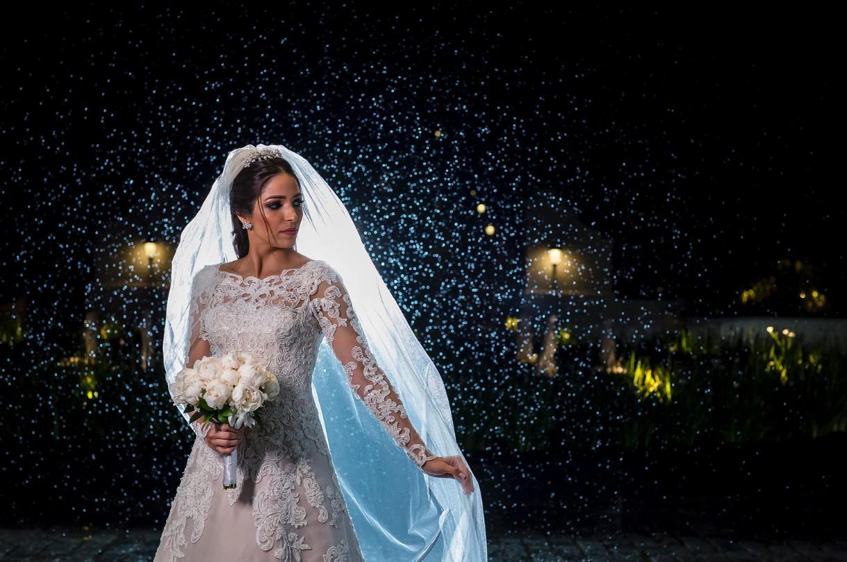 noiva posando com o vestido, o véu e o buquê