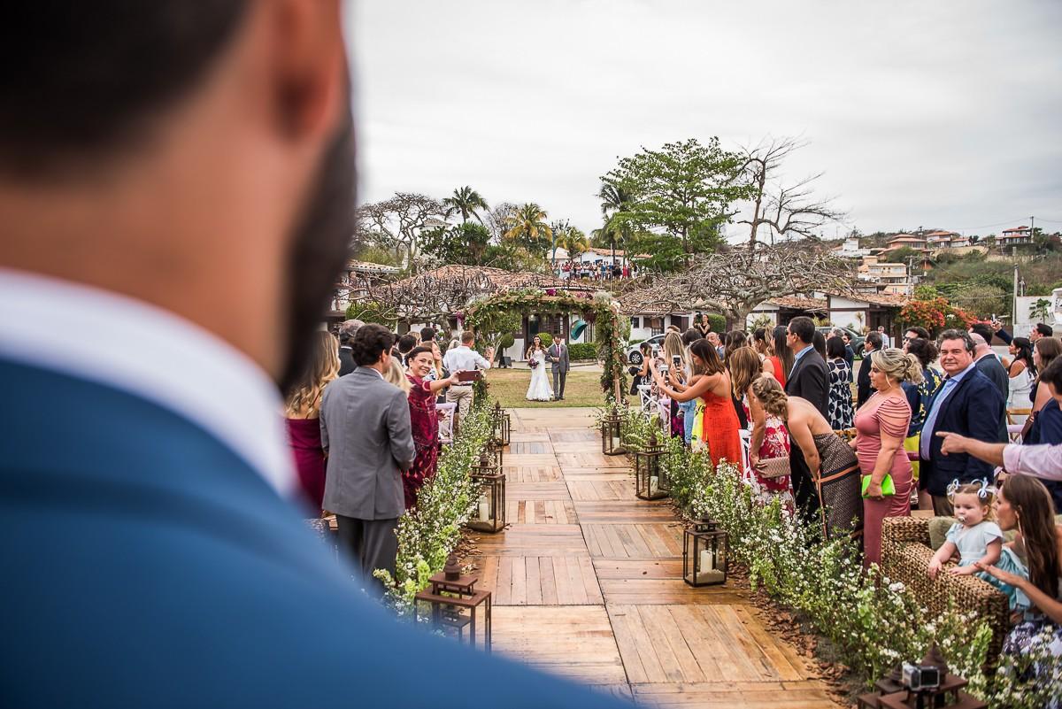 noivo observando a noiva caminhar até o altar com o pai
