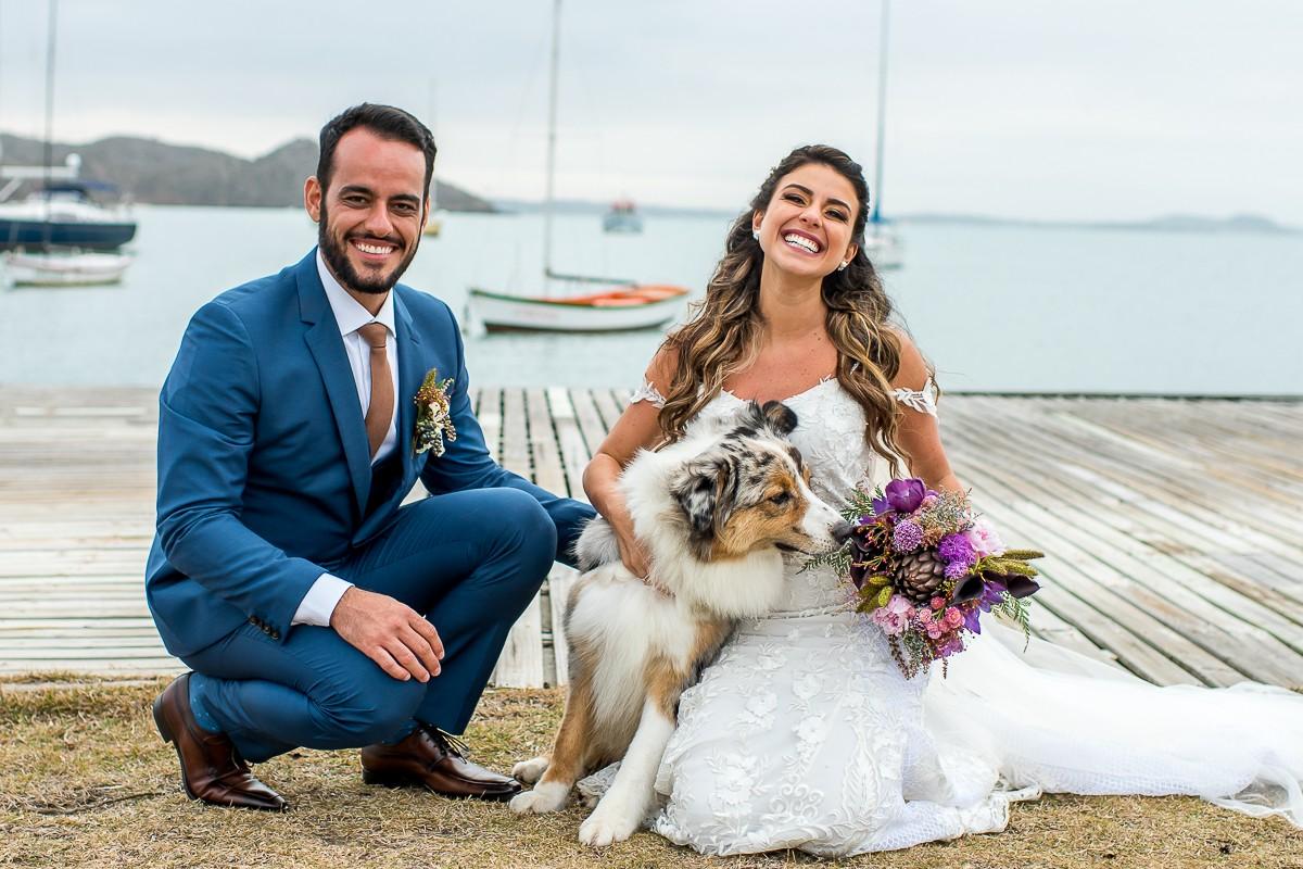 noivos posando com o cachorro de estimação após a cerimônia do casamento