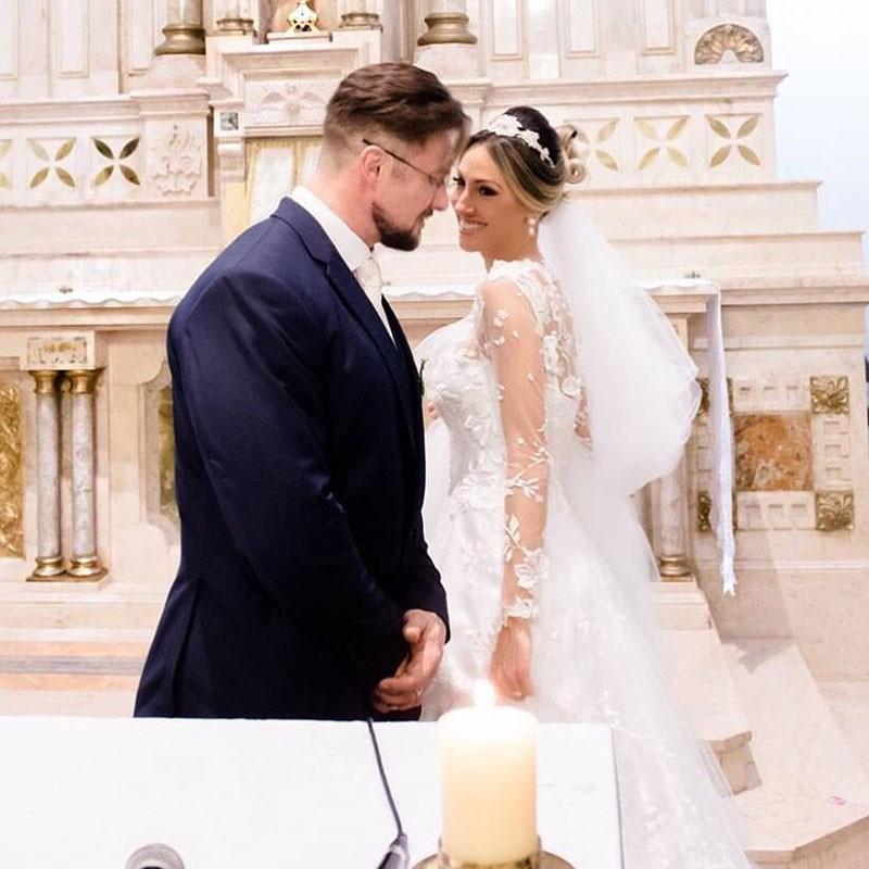 Paulo Muzy e Roberta Carbonari posam para foto após cerimônia religiosa.