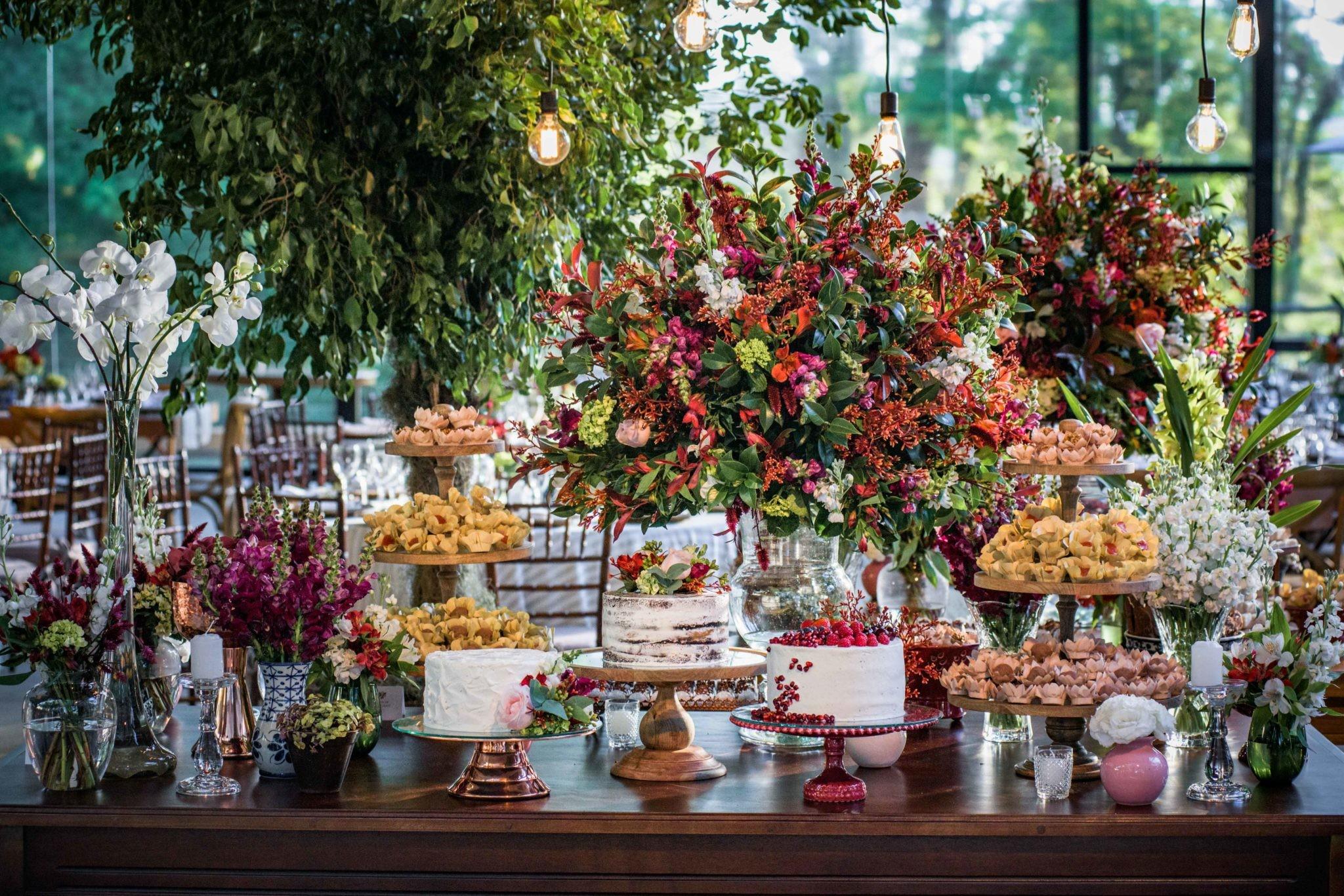 Mesa de doces decorada com flores em casamento moderno.
