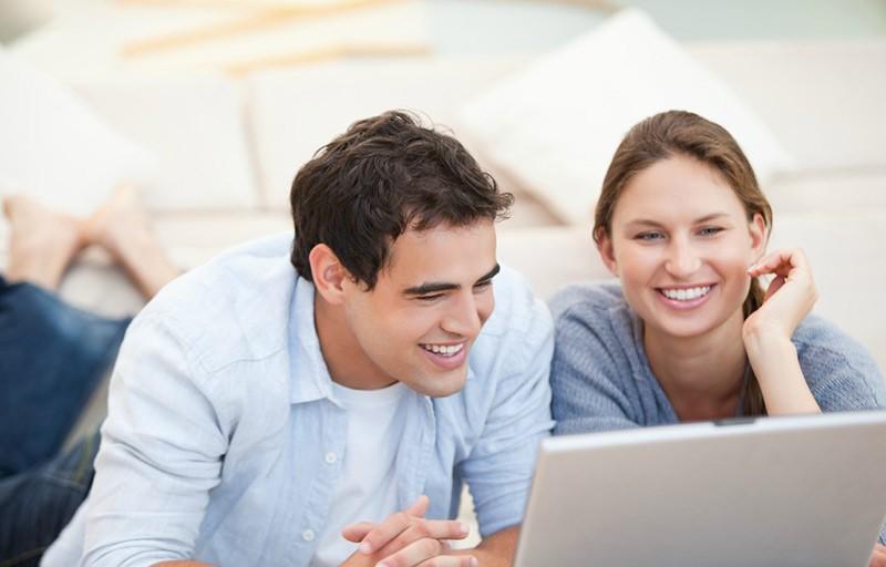 Casal preparando lista de casamento no computador.